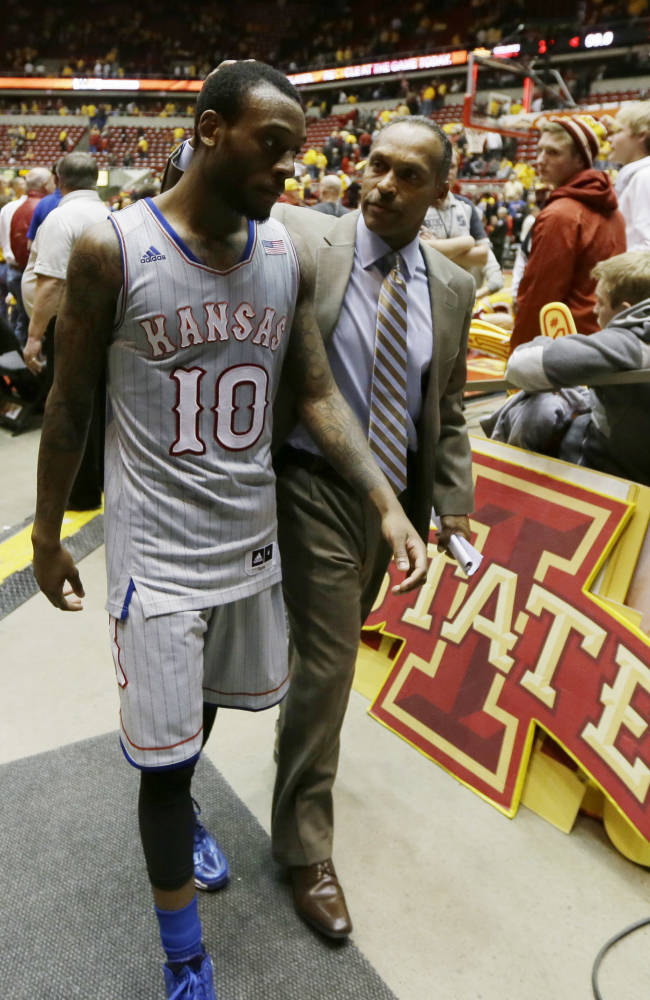 Kansas guard Naadir Tharpe walks off the court with assistant coach Norm Roberts after an NCAA college basketball game against Iowa State, Monday, Jan. 13, 2014, in Ames, Iowa. Tharpe scored 23 points as Kansas won 77-70