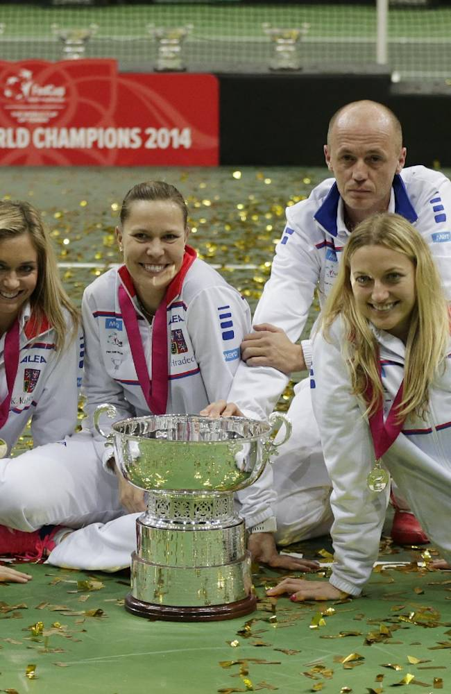 Czech Republic's team, left to right, Lucie Safarova, Klara Koukalova, Lucie Hradecka, Petr Pala, Petra Kvitova and Andrea Hlavackova celebrate with the trophy after defeating Germany in their Fed Cup Final tennis match in Prague, Czech Republic, Sunday, Nov. 9, 2014