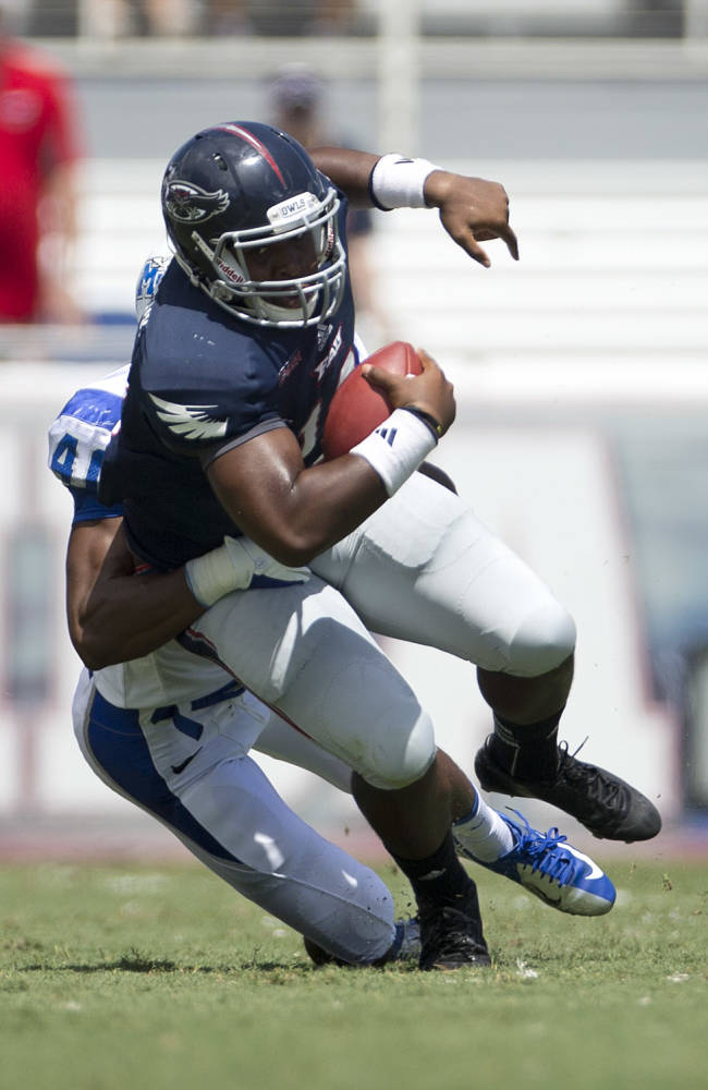 MIddle Tennessee's Leighton Gasque (40) stops Florida Atlantic quarterback Jaquez Johnson (12) after a short gain during the first half of a NCAA football game in Boca Raton, Fla., Saturday, Sept. 21, 2013