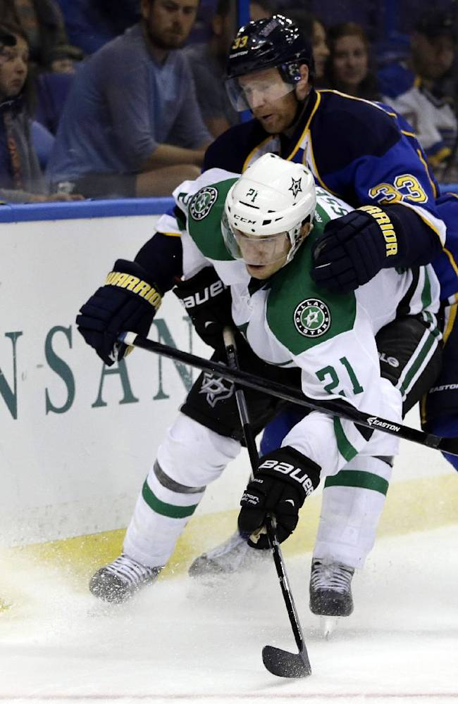 Dallas Stars' Antoine Roussel, front, of France, and St. Louis Blues' Jordan Leopold, right, chase after a loose puck during the third period of a preseason NHL hockey game Saturday, Sept. 21, 2013, in St. Louis. The Blues won 3-2 in overtime