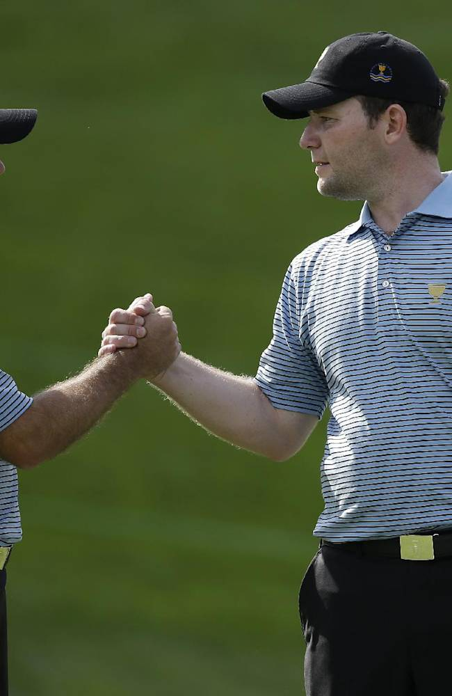 International team player Richard Sterne, left, of South Africa, and shakes hands with team player Branden Grace, of South Africa, following a practice round for the Presidents Cup golf tournament at Muirfield Village Golf Club Tuesday, Oct. 1, 2013, in Dublin, Ohio