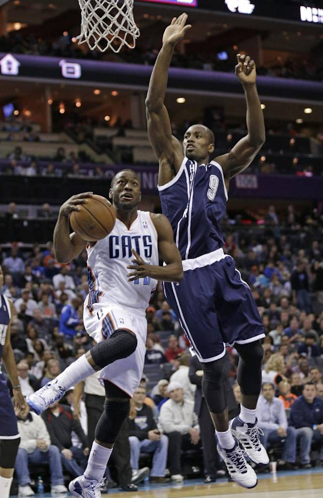 Charlotte Bobcats' Kemba Walker (15) drives past Oklahoma City Thunder's Serge Ibaka (9) during the first half of an NBA basketball game in Charlotte, N.C., Friday, Dec. 27, 2013