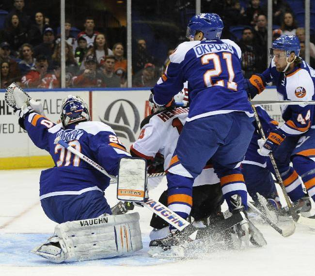 New Jersey Devils' Adam Henrique (14) shoots the puck past New York Islanders goalie Evgeni Nabokov (20) as Islanders'  Kyle Okposo (21) and Calvin de Haan (44) watch from behind in the first period of an NHL hockey game on Saturday, March 1, 2014, in Uniondale, N.Y