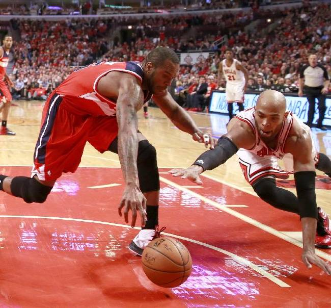 Washington Wizards forward Trevor Booker, left, and Chicago Bulls forward Taj Gibson scramble for a loose ball during the second half of Game 2 in an opening-round NBA basketball playoff series Tuesday, April 22, 2014, in Chicago. The Wizards won 101-99