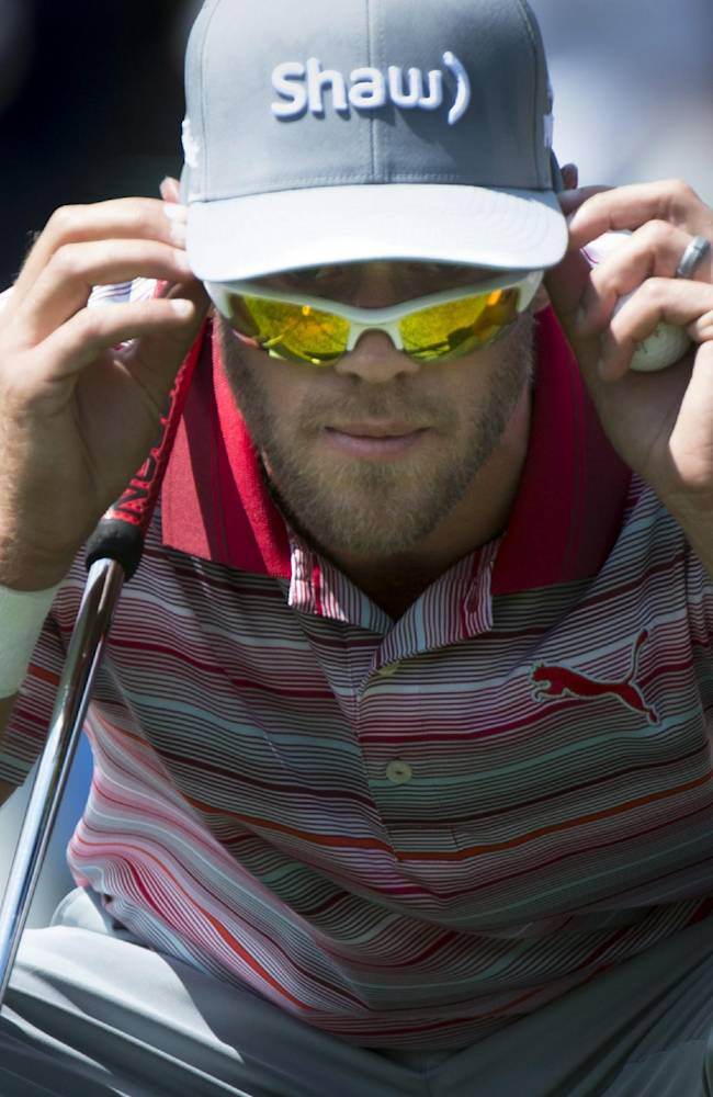 Graham DeLaet checks his line while on the second green during third-round of play at the Canadian Open golf championship in Montreal on Saturday, July 26, 2014