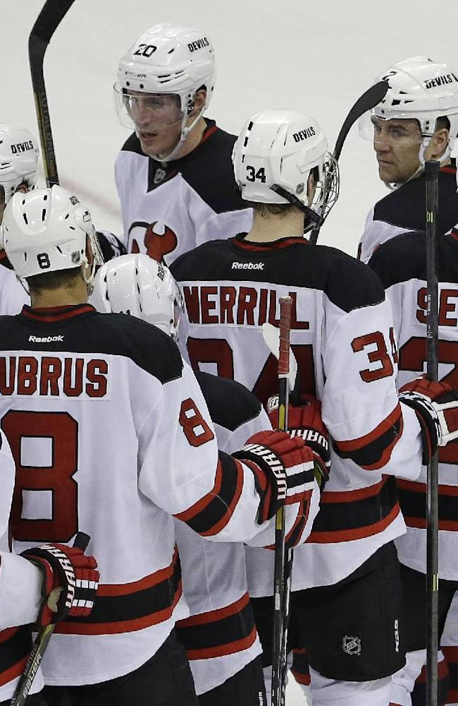 New Jersey Devils goalie Cory Schneider (35) is congratulated by teammates following their 3-1 win over the Carolina Hurricanes in an NHL hockey game in Raleigh, N.C., Saturday, April 5, 2014