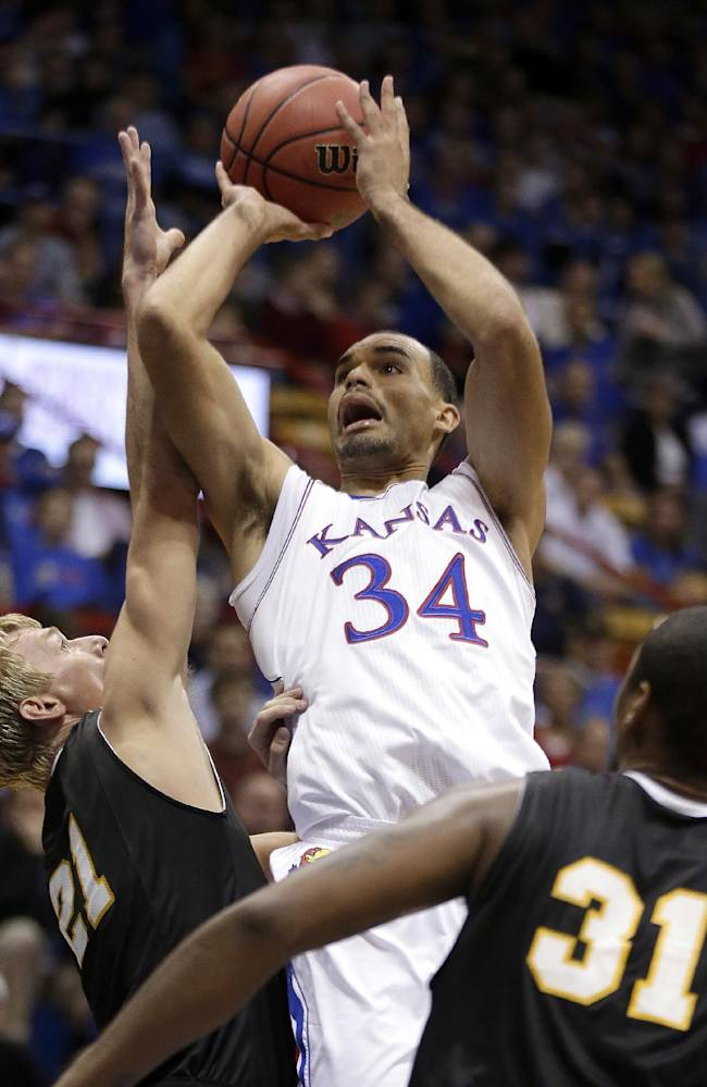 Kansas' Perry Ellis (34) puts up a shot between Fort Hays State's Jake Stoppel (21) and Dwayne Brunson (31) during the first half of an exhibition NCAA college basketball game Tuesday, Nov. 5, 2013, in Lawrence, Kan