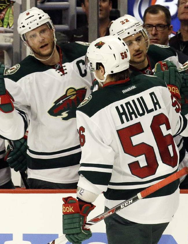 Minnesota Wild's Erik Haula (56) celebrates with teammates on the bench after scoring his goal against the Chicago Blackhawks during the first period  in Game 5 of an NHL hockey second-round playoff series in Chicago, Sunday, May 11, 2014
