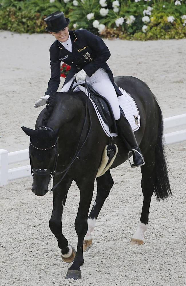 Kristina Sprehe of Germany, pats her horse Desperados after their presentation during the first day of the Dressage team competition at the FEI World Equestrian Games, at Michel d'Ornano stadium in Cean, western France, Monday, Aug. 25, 2014