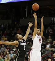 Washington State's Dexter Kernich-Drew (10) attempts a jump shot against Colorado's Xavier Talton (3) during the first half of an NCAA college basketball game Wednesday, Jan. 8, 2014, in Spokane, Wash. (AP Photo/Young Kwak)