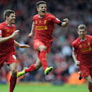 Liverpool's Philippe Coutinho, centre, celebrates with teammate Steven Gerrard, left, after he scored the third goal of the game for his side during their English Premier League soccer match against Manchester City at Anfield in Liverpool, England, Sunday