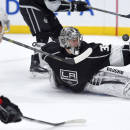 Los Angeles Kings goalie Jonathan Quick, right, deflects a shot by Calgary Flames left wing Mason Raymond, left, during the third period of an NHL hockey game, Monday, Dec. 22, 2014, in Los Angeles. The Flames won 4-3 in overtime. (AP Photo/Mark J. Terrill)