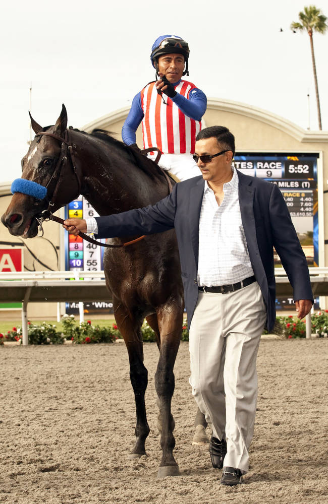 In this image provided by Benoit Photo, owner Kaleem Shah, right, guides Fed Biz, with Martin Garcia aboard, to the Winner's Circle after their victory in the Grade II, $200,000 San Diego Handicap horse race on Saturday, July 26, 2014, at Del Mar Thoroughbred Club in Del Mar, Calif