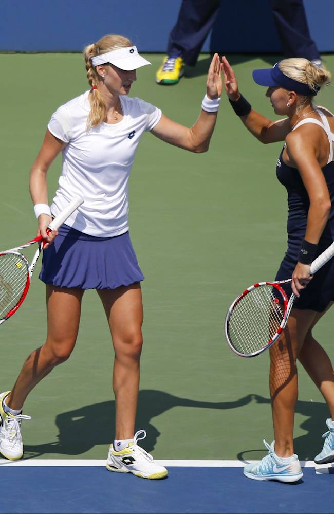 Ekaterina Makarova, of Russia, left, talks with Elena Vesnina, of Russia, between points against Kimiko Date-Krumm, of Japan, and Barbora Zahlavova Strycova, of the Czech Republic, during a semifinal doubles match of the 2014 U.S. Open tennis tournament, Thursday, Sept. 4, 2014, in New York