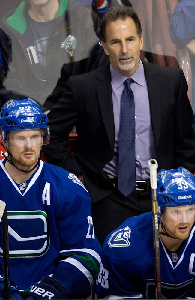 Vancouver Canucks' head coach John Tortorella, top, stands on the bench as Daniel Sedin, left, and his twin brother Henrik Sedin, both of Sweden, watch the play during third period NHL hockey action against the Boston Bruins in Vancouver, British Columbia, on Saturday, Dec. 14, 2013