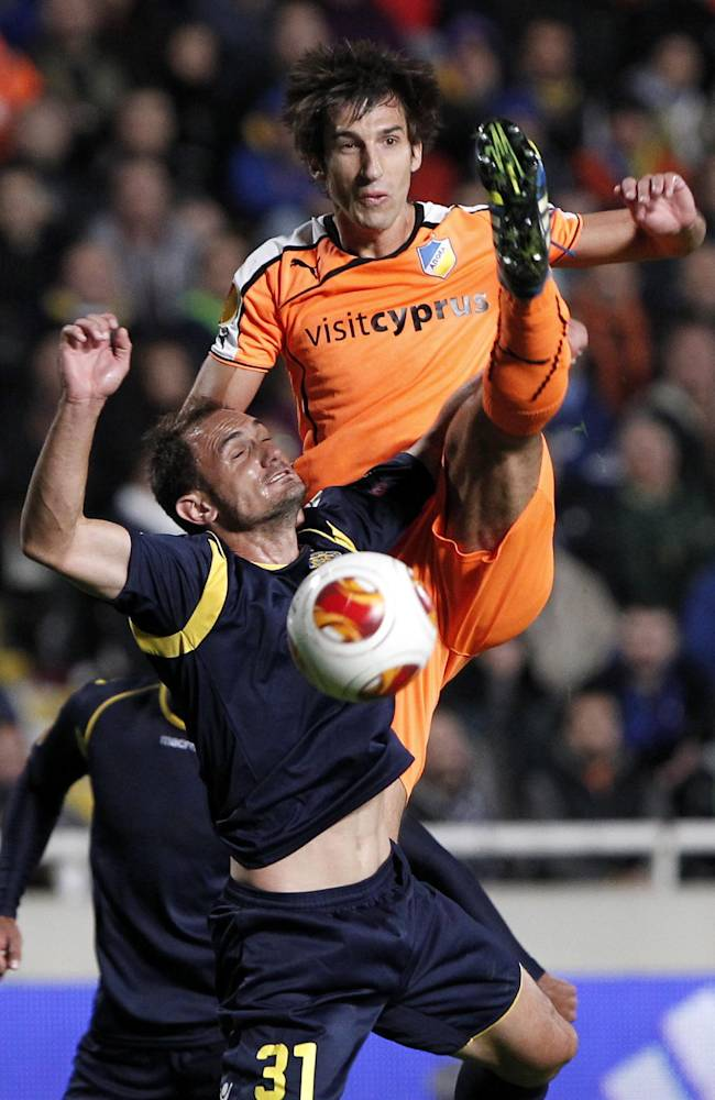 APOEL F.C's Hartiz Borda, rear, fights for the ball with Carlos Carcia of Maccabi Tel-Aviv during their Europa League group F soccer match at GSP stadium in Nicosia, Cyprus, Thursday, Nov. 28, 2013