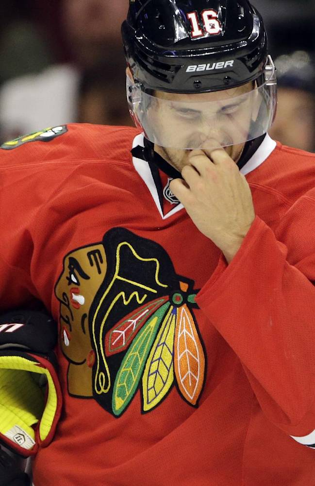 Chicago Blackhawks' Marcus Kruger reacts as he skates on the ice during the first period of an NHL preseason hockey game against the Pittsburgh Penguins in Chicago, Thursday, Sept. 19, 2013