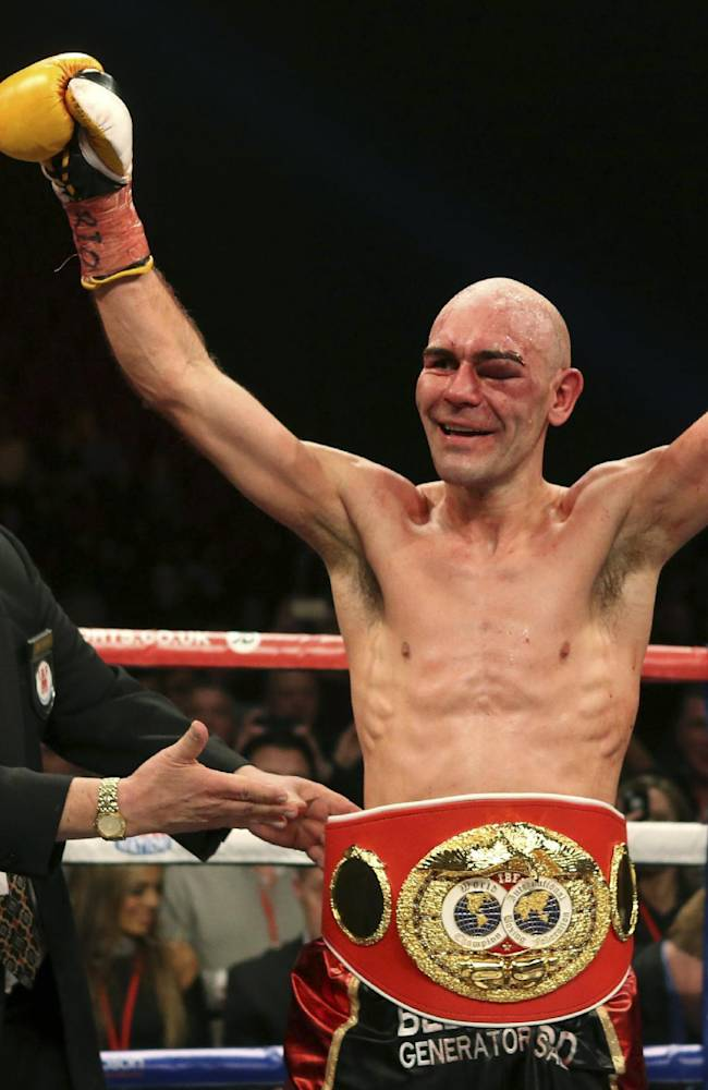 Britain's Stuart Hall raises his arms as he is presented with his belt after winning his IBF bantamweight title fight against South Africa's Vusi Malinga at the First Direct Arena, in Leeds, England, Saturday Dec. 21, 2013. Hall claimed the vacant IBF bantamweight title on Sunday after a points win over Malinga
