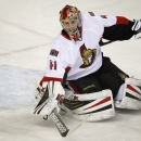 Ottawa Senators goalie Craig Anderson dives for the puck during the first period of an NHL hockey game against the Calgary Flames on Wednesday, March 5, 2014, in Calgary, Alberta The Associated Press