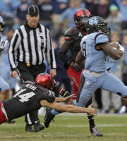 North Carolina's T.J. Logan (8) runs past Cincinnati's Tony Miliano (14) as he returns a kick for a touchdown during the first half of the Belk Bowl NCAA college football game, Saturday, Dec. 28, 2013, in Charlotte, N.C. (AP Photo/Chuck Burton)