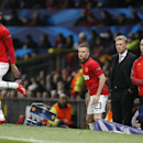 Manchester United's Robin van Persie, left warms up as he is about to come on to play as a substitute during their Champions League group A soccer match between Manchester United and Shakhtar Donetsk at Old Trafford Stadium, Manchester, England, Tuesday,