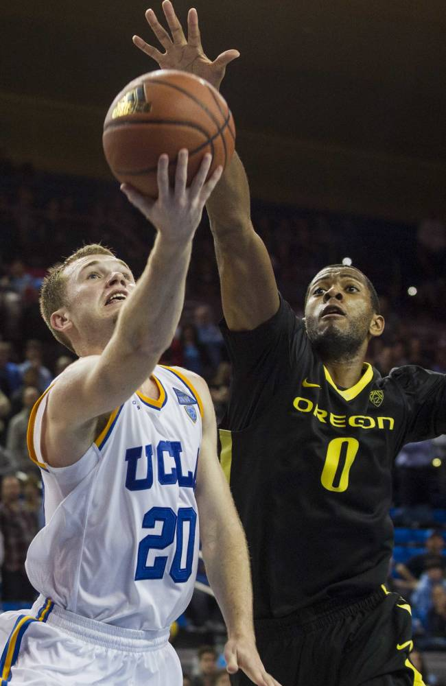 UCLA guard Bryce Alford, left, goes up for a lay up against Oregon forward Mike Moser in the second half of an NCAA college basketball game Thursday, Feb. 27, 2014, in Los Angeles. Oregon 87-83 double overtime win over UCLA. Alford scored a game-hight 31 points