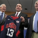 Duke University basketball coach Mike Krzyzewski, center, holds a Team USA jersey, as he is flanked by school President Richard Broadhead, left, and Director of Athletics Kevin White at a news conference in Durham, N.C., Thursday, May 23 2013. Krzyzewski is back as the U.S. men's national team coach and ready for another run at Olympic gold. (AP Photo/The News & Observer, Corey Lowenstein)