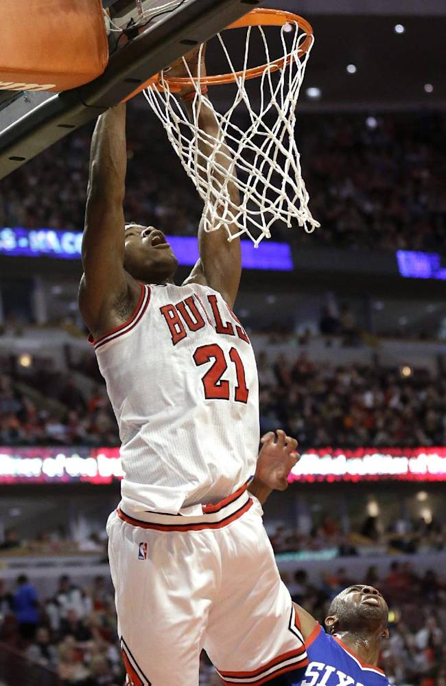 Chicago Bulls guard Jimmy Butler (21) goes up for a dunk as Philadelphia 76ers guard James Anderson (9) looks on during the second half of an NBA basketball game in Chicago on Saturday, March 22, 2014. The Bulls won 91-81