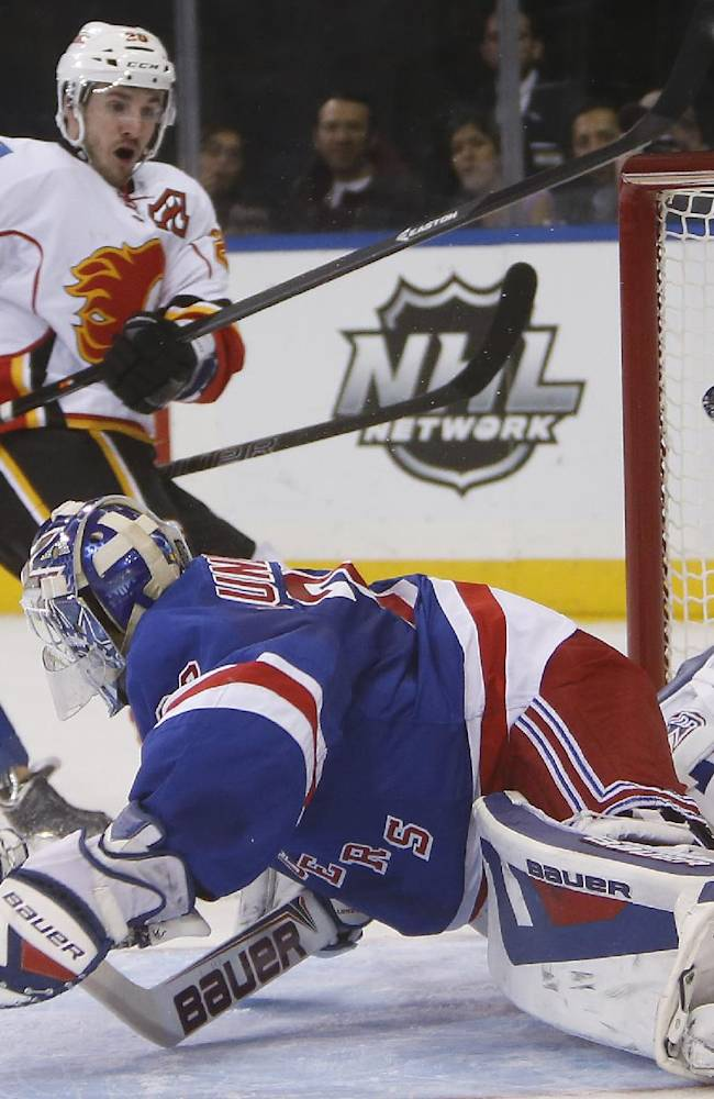 Calgary Flames' Curtis Glencross, second from left, scores a goal against New York Rangers goalie Henrik Lundqvist, of Sweden, during the first period of an NHL hockey game Sunday, Dec. 15, 2013, in New York