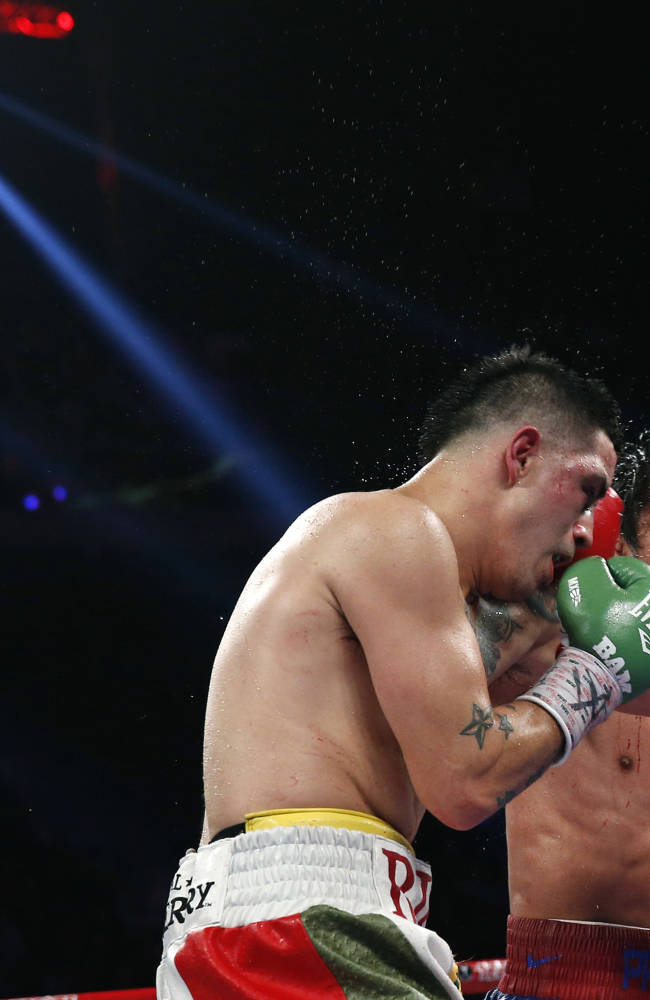Manny Pacquiao from the Philippines, right, lands a right to Brandon Rios of the United States during their WBO international welterweight title fight Sunday, Nov. 24, 2013, in Macau. Pacquiao defeated Rios by unanimous decision on Sunday to take the WBO international welterweight title and return to his accustomed winning ways after successive defeats