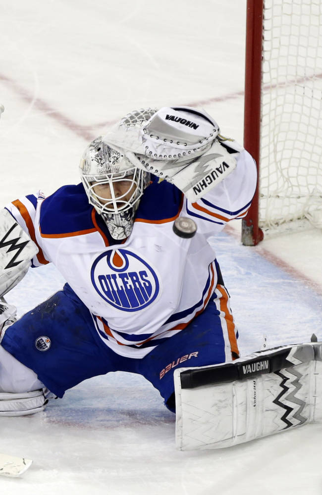 CORRECTS TO OILERS GOALIE BEN SCRIVENS NOT RICHARD BACHMAN - Edmonton Oilers goalie Ben SCrivens (30) deflects a shot on-goal during the third period of an NHL hockey game against the New York Rangers, Thursday, Feb. 6, 2014, in New York. The Oilers won the game 2-1