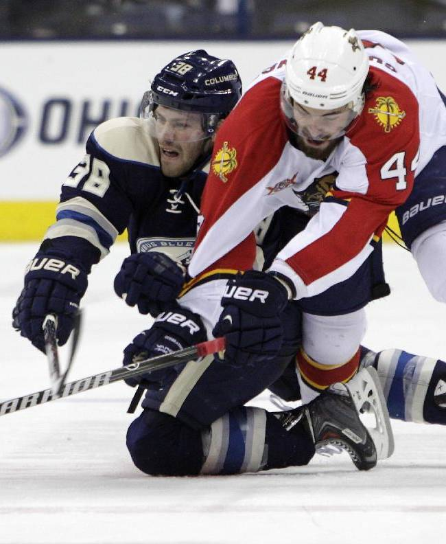 Florida Panthers' Erik Gudbranson, right, and Columbus Blue Jackets' Boone Jenner chase a loose puck during the second period of an NHL hockey game Saturday, Feb. 1, 2014, in Columbus, Ohio
