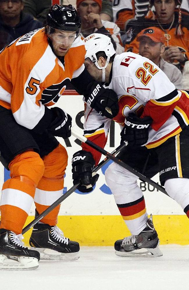 Philadelphia Flyers' Braydon Coburn, left, and Calgary Flames' Lee Stempniak, right, dig for the loose puck along the boards during the first period of an NHL hockey game, Saturday, Feb. 8, 2014, in Philadelphia