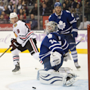Toronto Maple Leafs goaltender James Reimer makes a save as defenseman Cody Franson and Chicago Blackhawks Jonathan Toews (19) look on during the third period of an NHL hockey game in Toronto on Saturday, Nov. 1, 2014 The Associated Press