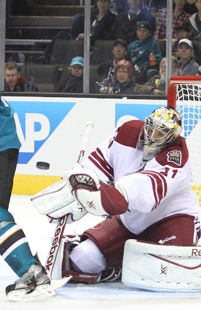 The Sharks' Logan Couture screens Coyote goalie Mike Smith during an NHL preseason hockey game in San Jose, Calif., Saturday, Sept. 21, 2013. The Sharks won 3-2 in overtime