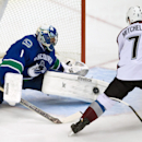 Vancouver Canucks' goalie Roberto Luongo, left, stops Colorado Avalanche's John Mitchell during second period of an NHL hockey game in Vancouver, British Columbia on Sunday, Dec. 8, 2013 The Associated Press