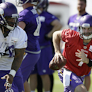 Minnesota Vikings quarterback Christian Ponder, right, runs from defensive tackle Isame Faciane during NFL football training camp, Saturday, July 26, 2014, in Mankato, Minn The Associated Press
