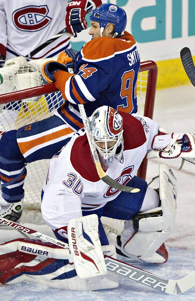 Montreal Canadians' Peter Budaj (30) makes the save as Edmonton Oilers' Ryan Smyth (94) hangs off the crossbar during first-period NHL hockey game action in Edmonton, Alberta, Thursday, Oct. 10, 2013. (AP {Photo/The Canadian Press, Jason Franson)