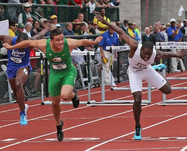 In this June 14, 2014, file photo, Oregon's Devon Allen, front left, and Texas A&M's Wayne Davis II reach for the finish line during the men's 110-meter hurdles at the NCAA track and field championships on, in Eugene, Ore. In June, Allen won the NCAA championship in the 110-meter hurdles. Two months later, he's won the job a starting receiver for the No. 3 Ducks. Allen, a redshirt freshman, will start along with senior Keanon Lowe at receiver when Oregon hosts South Dakota in the opener on Saturday night