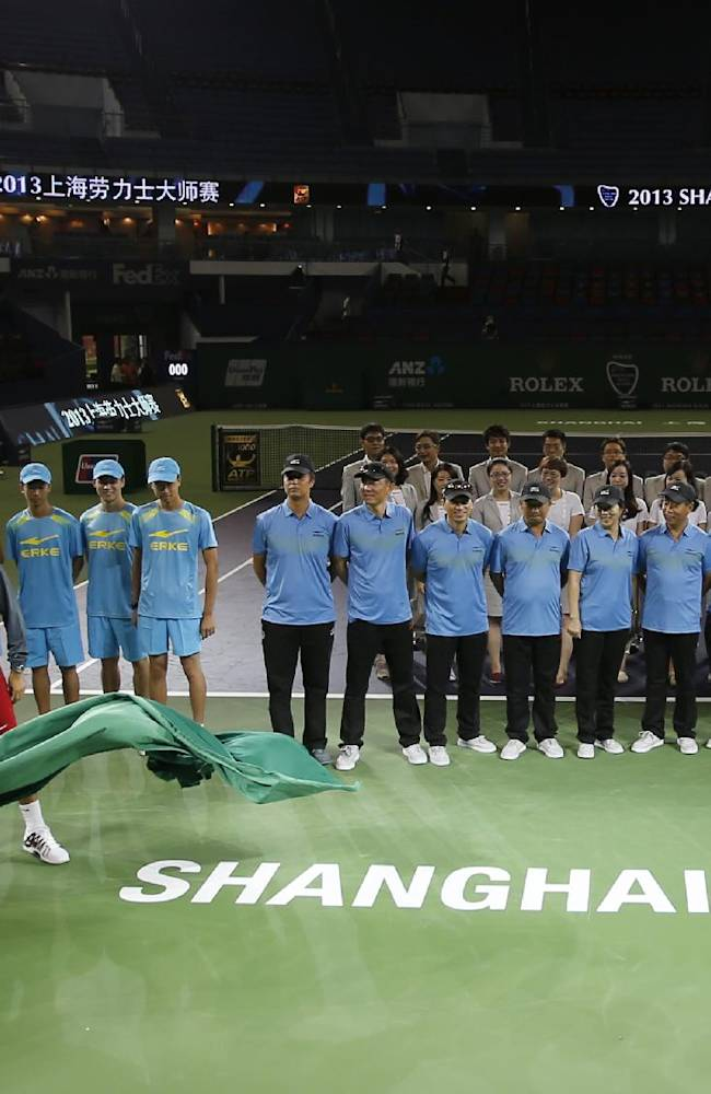 Roger Federer of Switzerland, left, pulls a cover during an unveiling ceremony ahead of the Shanghai Rolex Masters at Qizhon Tennis Center in Shanghai, China, Saturday, Oct. 5, 2013