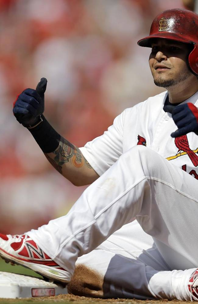 St. Louis Cardinals' Yadier Molina celebrates as he looks into the dugout after hitting a two-run single during the fourth inning of a baseball game against the Washington Nationals Wednesday, Sept. 25, 2013, in St. Louis