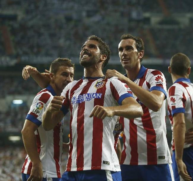 Atletico's Raul Garcia, center, celebrates his goal with teammates during a Spanish Supercup first leg soccer match against Real Madrid at Santiago Bernabeu stadium in Madrid, Spain, Tuesday, Aug. 19, 2014