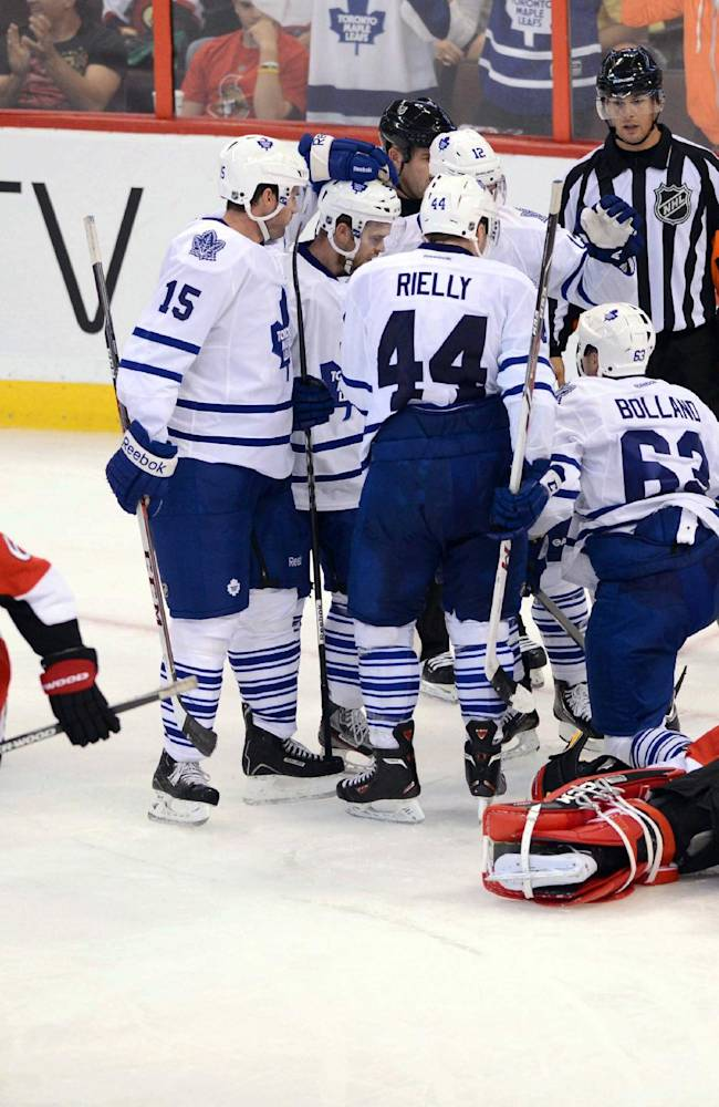Ottawa Senators goalie Nathan Lawson lies on the ice after letting in the game winning goal by Toronto Maple Leafs' Dave Bolland, second from the right, who celebrates with teammates during a preseason NHL hockey game in Ottawa, Ontario on Thursday, Sept. 19, 2013. The Leafs defeated the Senators 3-2