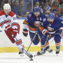 Carolina Hurricanes center Brad Malone (24) skates up the ice with New York Islanders right wing Kyle Okposo (21) and defenseman Nick Leddy (2) in tow in the first period of a NHL hockey game, Saturday, Oct. 11, 2014, in Uniondale, N.Y The Associated Pres