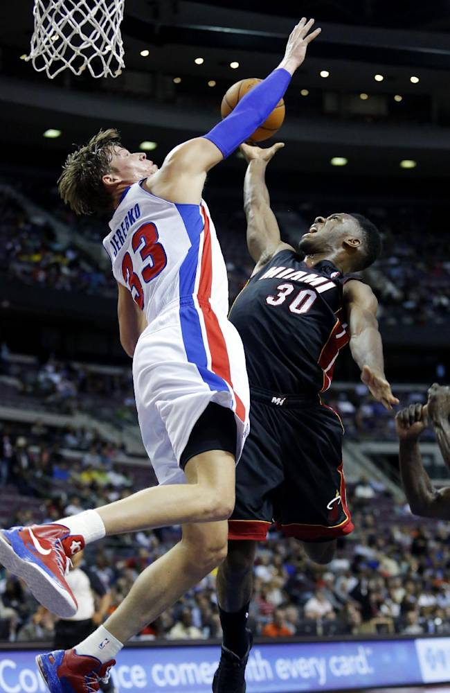 Detroit Pistons forward Jonas Jerebko (33), of Sweden, defends against a shot by Miami Heat guard Norris Cole (30) in the first half of an NBA basketball preseason game on Thursday, Oct. 10, 2013, in Detroit