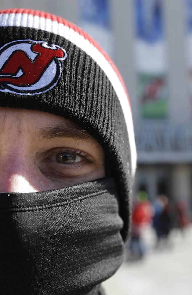 A New Jersey Devils fan arrives bundled up for an outdoor NHL hockey game between the New Jersey Devils and the New York Rangers Sunday, Jan. 26, 2014, at Yankee Stadium in New York
