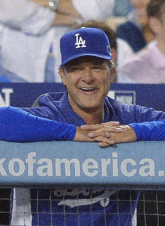 In this Oct. 14, 2013 file photo, Los Angeles Dodgers manager Don Mattingly smiles during a pitching change in the eighth inning of Game 3 of the National League baseball championship series against the St. Louis Cardinals, in Los Angeles. Mattingly will be back as manager of the Los Angeles Dodgers next season with a new three-year contract that takes him through 2016