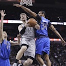 San Antonio Spurs' Tiago Splitter (22), of Brazil, drives between Dallas Mavericks defenders Dirk Nowitzki (41) and Brandan Wright (34) during the first half of an NBA basketball game, Sunday, March 2, 2014, in San Antonio The Associated Press