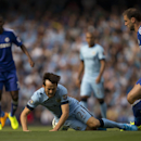 Manchester City's David Silva, center, is felled by Chelsea's Branislav Ivanovic, right, during their English Premier League soccer match at the Etihad Stadium, Manchester, England, Sunday Sept. 21, 2014