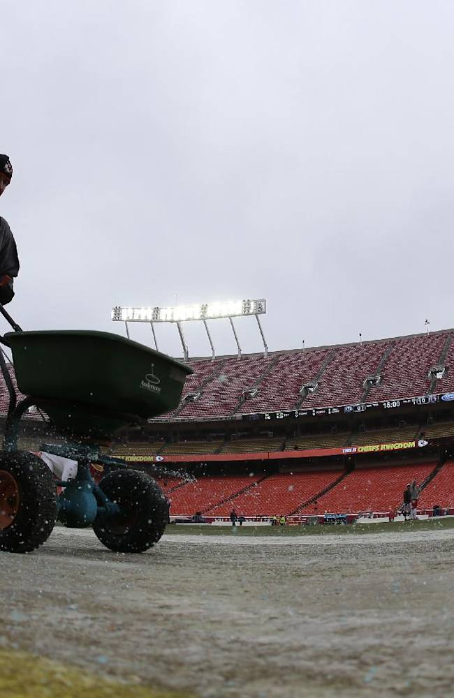 A worker applies ice melt to the sidelines before an NFL football game between the Kansas City Chiefs and the Indianapolis Colts Sunday, Dec. 22, 2013, in Kansas City, Mo